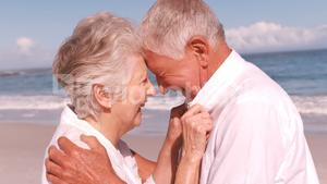 Elderly couple embracing on the beach