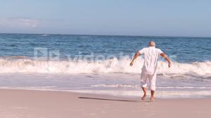 Elderly man running and jumping on the beach