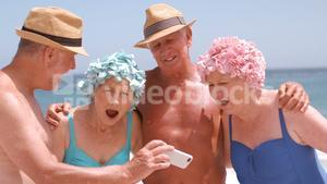 senior friends looking a smartphone and laughing