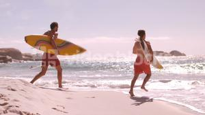 Two surfers running to go in the water