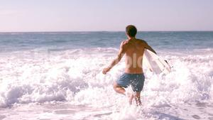 Surfer running to go in the water