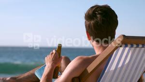 Man drinking a beer on his deckchair