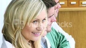 Medical team in a row and friendly blonde doctor smiling