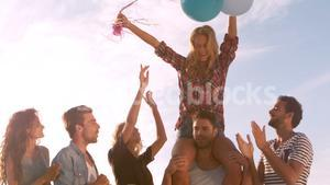 Woman siting on mans shoulders holding air balloons
