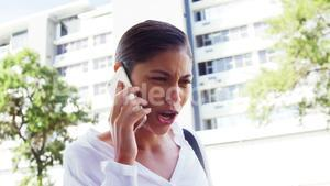 woman talking on phone with city background