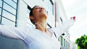 Woman outdoors raising arms in joy with building background