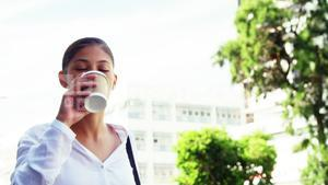 Woman sipping coffee on street