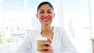 smiling woman sipping coffee in office