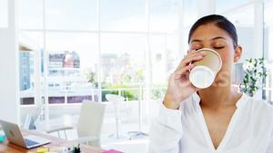 Woman sipping coffee with office background