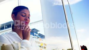 woman looking out office window and using smart device