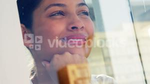 Smiling woman looking out office window