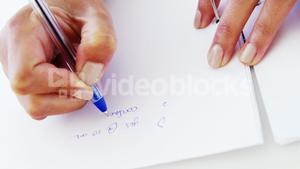 woman taking notes on blank paper