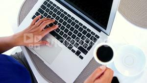 woman using laptop and putting down coffee