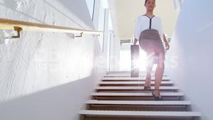 Woman walking down stairs with suitcase