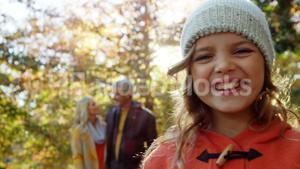 Smiling girl with happy parents in backgrounds