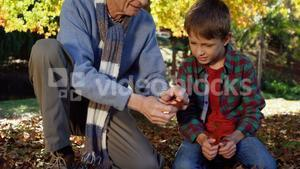 grandfather and grandson playing with leaves