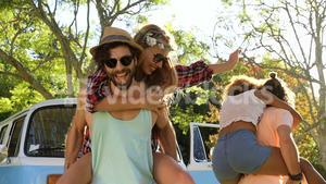 Hipster boys carrying girls on their shoulders