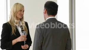 Businesswoman and businessman talking in a business celebration