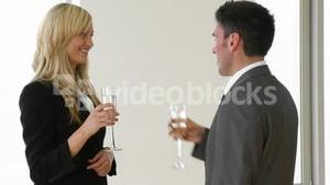 Businesswoman and businessman celebrating a success with champagne