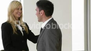 Businesswoman and businessman shaking hands in office footage