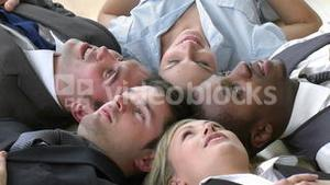 Footage of Business team relaxing on floor in office