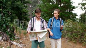 Couple of hiker looking a map and compass
