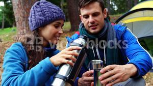 Hiker woman serving coffee to her husband
