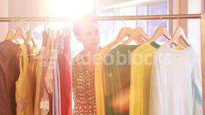 Woman selecting clothes from clothing rack