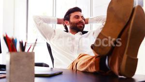 Male executive sitting with legs on table