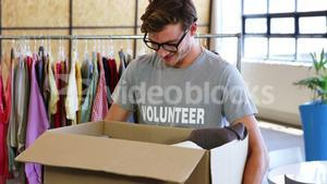 Volunteer holding clothes donation box in office