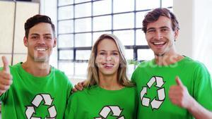 Volunteers wearing green ecologic t-shirt showing thumbs up