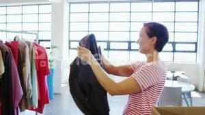 Woman arranging clothes on clothing rack