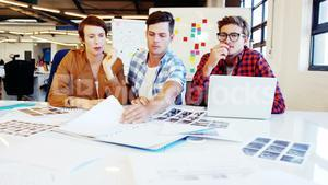 Graphic designer holding photo sample and interacting with colleagues
