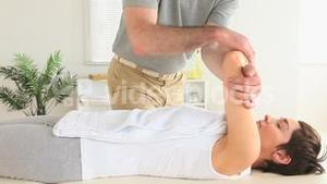 Chiropractor stretching the shoulder of a woman