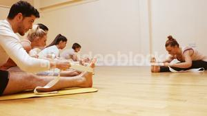 Trainer helping group of people with stretching exercise
