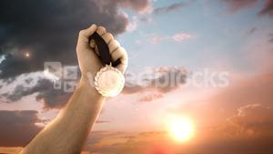 Hand of athlete holding gold medal