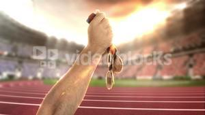 Hand of athlete holding gold medals