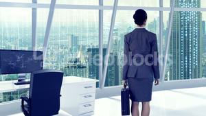 Businesswoman looking at digitally generated text and graphic on office window