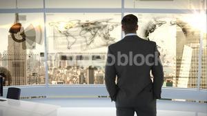 Businessman looking at digitally generated text and graphic on office window
