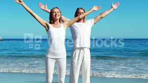 Couple standing with arms outstretched at beach