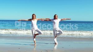 Couple performing yoga at beach