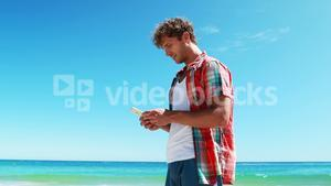 Man talking on mobile phone at beach