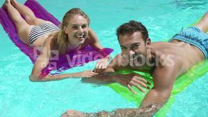 Couple relaxing together in swimming pool