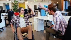 Businessman in wheelchair giving high five to coworkers