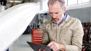 Mechanic using digital tablet while servicing a car engine