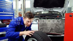 Mechanic checking tyre and making ok sign
