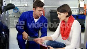 Mechanic showing customer the problem with car