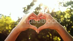 Hands of woman forming a heart shape