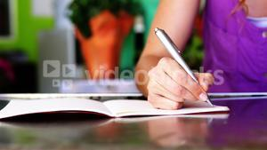 Female florist writing in book