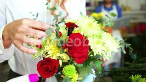 Female florist arraigning flower in flower vase